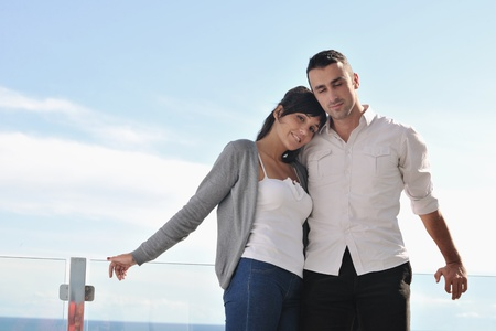 happy young couple in love have romance  relax on balcony outdoor with ocean and blue sky in background Stock Photo - 11398922