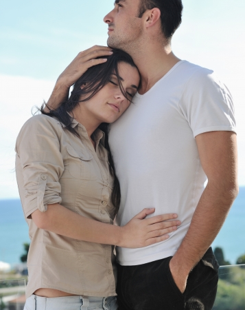 happy young couple in love have romance  relax on balcony outdoor with ocean and blue sky in background Stock Photo - 16393514