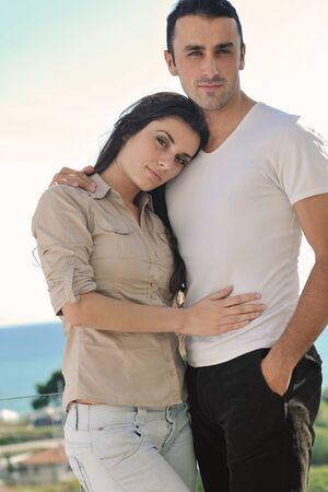 happy young couple in love have romance  relax on balcony outdoor with ocean and blue sky in background Stock Photo - 16393537