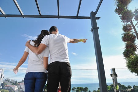 happy young couple in love have romance  relax on balcony outdoor with ocean and blue sky in background Stock Photo - 11398931