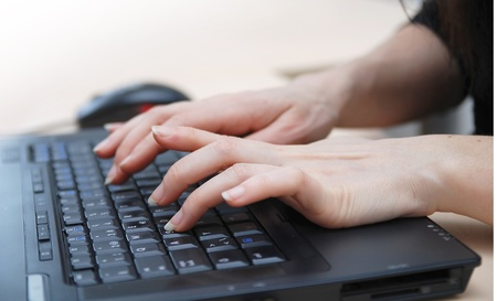 typist: woman hands typing on laptop keyboard Stock Photo