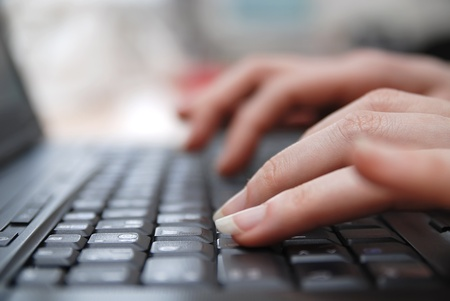 woman hands typing on laptop keyboard photo