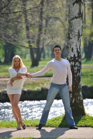 Stock Photo - happy young romantic couple in love dance outdoor at spring season on early mornig with beautiful light photo