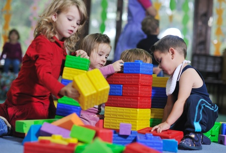 preschool education: happy child kids group have fun and play at kindergarden indoor preschool education concept with  teacher