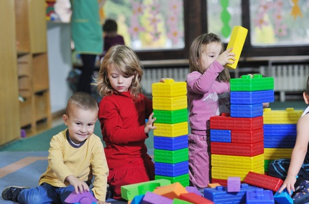 children playing together: happy child kids group have fun and play at kindergarden indoor preschool education concept with  teacher