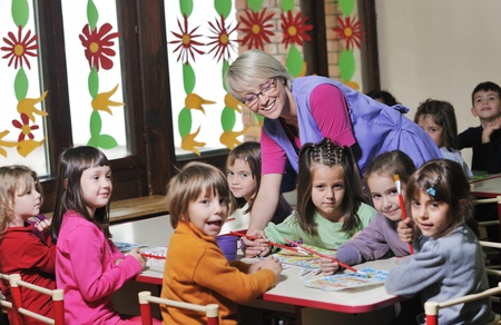 preschool: happy child kids group have fun and play at kindergarden indoor preschool education concept with  teacher