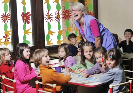 class room: happy child kids group have fun and play at kindergarden indoor preschool education concept with  teacher