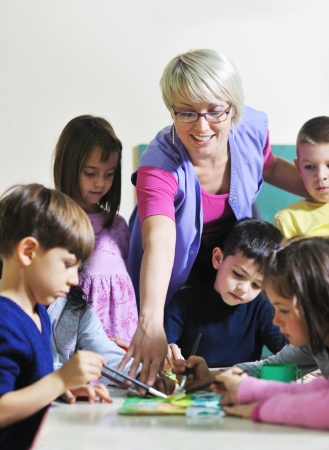happy child kids group have fun and play at kindergarden indoor preschool education concept with  teacher photo