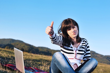 laptop outside: young teen girl read book and study homework outdoor in nature with blue sky in background Stock Photo