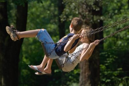 niña y niño de desafío en el columpio en el parque Foto de archivo