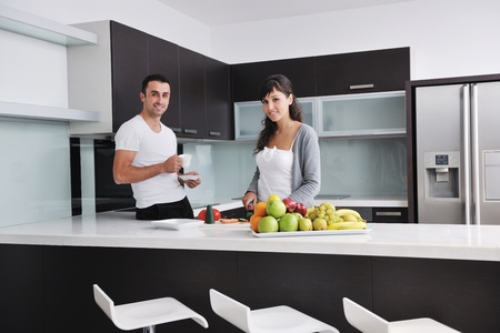 family in kitchen: happy young couple have fun in  modern kitchen indoor  while preparing fresh fruits and vegetables food salad Stock Photo
