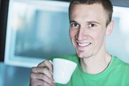 natural looking: handsome young man drink fresh morning coffee from white cup