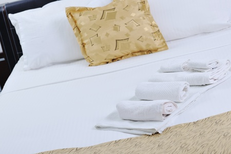 linen fabric: white towels on bed in luxury hotel room with yellow pillow in background