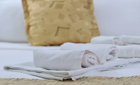 white towels on bed in luxury hotel room with yellow pillow in background Stock Photo - 11465611