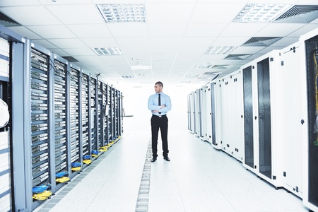 communications technology: young handsome business man  engeneer in datacenter server room