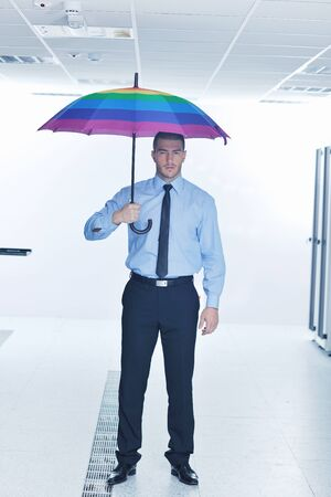 young handsome business man  engineer in .businessman hold  rainbow colored umbrella in server datacenter room  and representing security and antivirus sofware protection concept photo