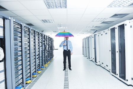 young handsome business man  engineer in .businessman hold  rainbow colored umbrella in server datacenter room  and representing security and antivirus sofware protection concept Stock Photo - 11399113