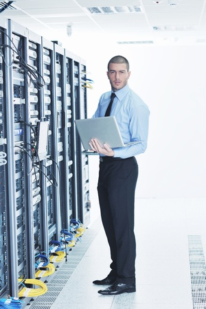 engeneer: young engeneer business man with thin modern aluminium laptop in network server room
