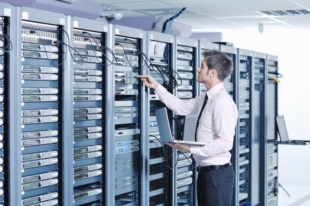 young engeneer business man with thin modern aluminium laptop in network server room Stock Photo - 11445649