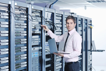 young engeneer business man with thin modern aluminium laptop in network server room photo