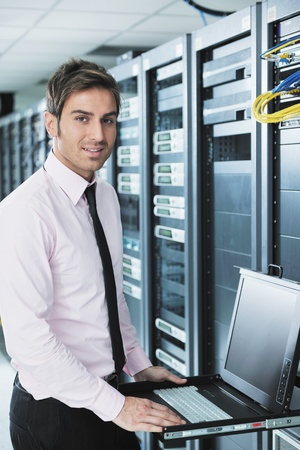 data backup: young engeneer business man with thin modern aluminium laptop in network server room
