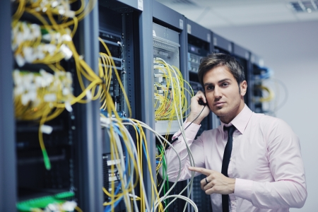 it technology: young business man computer science engeneer talking by cellphone at network datacenter server room asking  for help and fast solutions and services Stock Photo