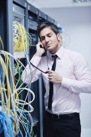 young business man computer science engeneer talking by cellphone at network datacenter server room asking  for help and fast solutions and services photo