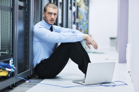 young engeneer business man with thin modern aluminium laptop in network server room Stock Photo - 11465413