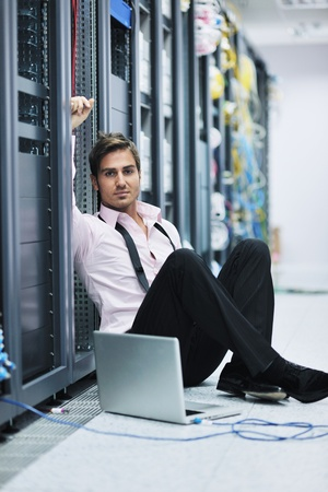 cable tie: young engeneer business man with thin modern aluminium laptop in network server room