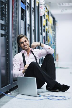 young engeneer business man with thin modern aluminium laptop in network server room Stock Photo - 11465458