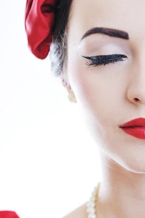 speld: mooie jonge vrouw geà ¯ soleerd op wit in studio in ouderwetse kleding die pinup en retro-stijl