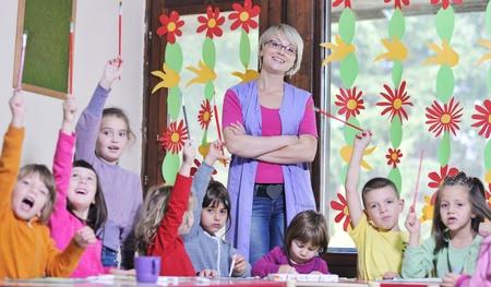 preschool teacher: happy child kids group have fun and play at kindergarden indoor preschool education concept with  teacher