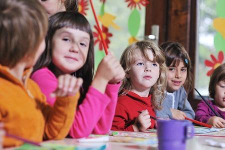ni�os dibujando: ni�o feliz grupo de ni�os se divierten y juegan en el jard�n de infancia en interiores concepto de la educaci�n preescolar con el maestro