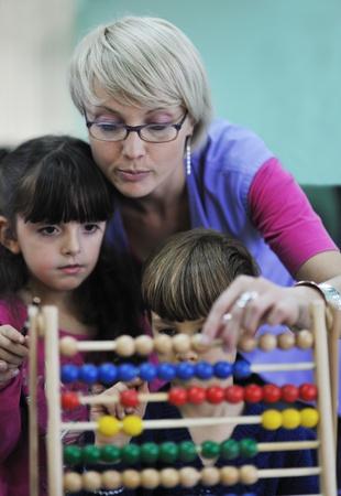 kindergarten toys: happy child kids group have fun and play at kindergarden indoor preschool education concept with  teacher