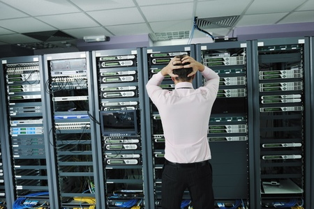 data backup: it business man in network server room have problems and looking for  disaster situation  solution