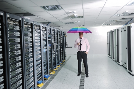 young handsome business man  engineer in .businessman hold  rainbow colored umbrella in server datacenter room  and representing security and antivirus sofware protection concept Stock Photo - 11718378