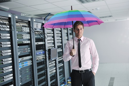 businessman hold  rainbow colored umbrella in server datacenter room  and representing security and antivirus sofware protection concept photo