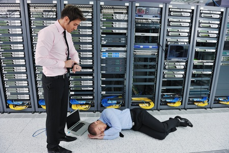 it business man in network server room have problems and looking for  disaster situation  solution photo