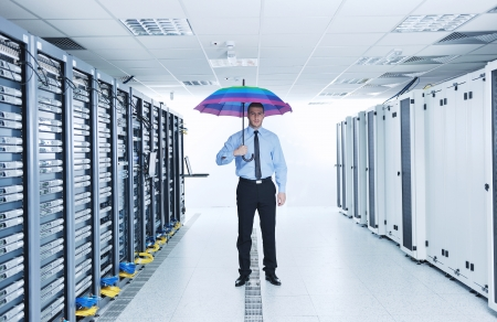 virtual server: young handsome business man  engineer in  businessman hold  rainbow colored umbrella in server datacenter room  and representing security and antivirus sofware protection concept Stock Photo