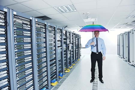 data recovery: young handsome business man  engineer in  businessman hold  rainbow colored umbrella in server datacenter room  and representing security and antivirus sofware protection concept Stock Photo
