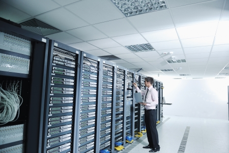 data backup: young handsome business man  engeneer in datacenter server room