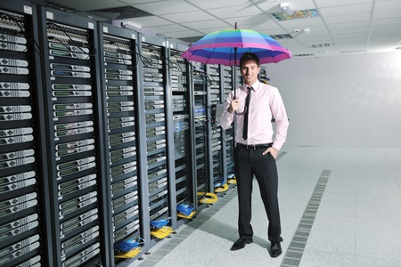 data recovery: young handsome business man  engineer in .businessman hold  rainbow colored umbrella in server datacenter room  and representing security and antivirus sofware protection concept Stock Photo