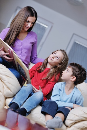 young mother read book to their kids at modern new home living room indoor photo