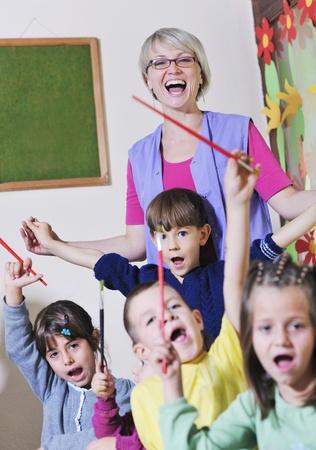 maestra preescolar: niño feliz grupo de niños se divierten y juegan en guardería cubierta concepto de educación preescolar con el maestro Foto de archivo