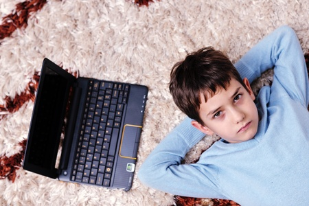 happy child boy relax at home with laptop computer in background photo