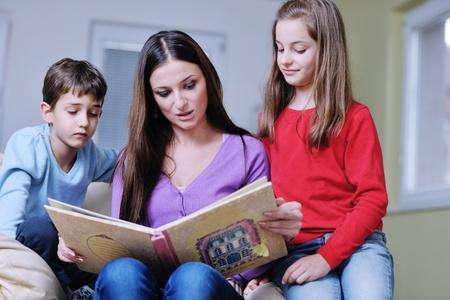 mamma e figlio: giovane madre leggere il libro ai propri figli a moderna sala nuova vivere la casa coperta