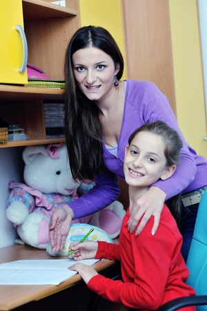 happy family woman and girl working on homework at home while mom showing globe and giving help photo