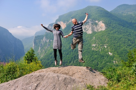 joy of life: happy young couple in love jump in air in beautiful green and fresh nature
