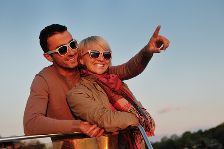 happy young couple in love  have romantic time at summer sunset   at ship boat while  representing urban and countryside fashin lifestyle Stock Photo - 12070170