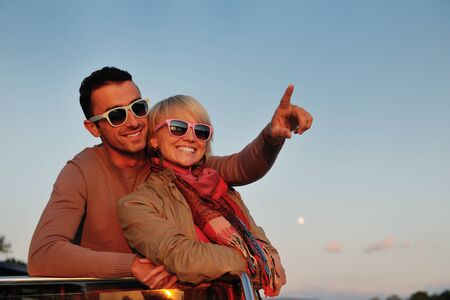 happy young couple in love  have romantic time at summer sunset   at ship boat while  representing urban and countryside fashin lifestyle Stock Photo - 12069621